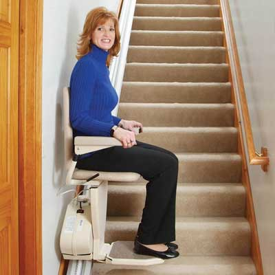 Woman in blue sweater sitting in the chair of a stairlift at the bottom of a staircase
